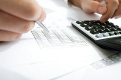 Counting income on calculator. Financial data analyzing. Counting business data on the table closeup Royalty Free Stock Images