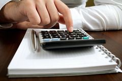 Counting income on calculator. Financial data analyzing. Counting business data on the table closeup Stock Photo