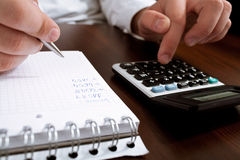 Counting income on calculator. Financial data analyzing. Counting business data on the table closeup Stock Photography