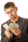 Counting money. Thoughtful businessman counting money (hundreds of dollars), isolated on  white background Stock Photos