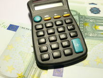 Counting money. Calculator lying on euro banknotes Royalty Free Stock Photography