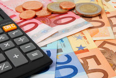 Counting money. Euro banknotes and coins and a calculator stock photography