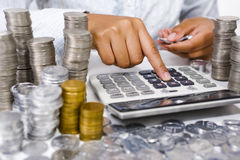 Counting money. Hand counting money using calculator with stack of coins around it. South East Asian coins used here royalty free stock photos