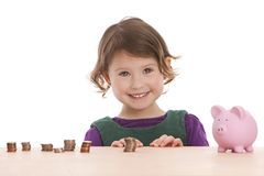 Counting Money. Adorable preschooler counting the money in her piggy bank.  Isolated on white with room for your text Royalty Free Stock Photos