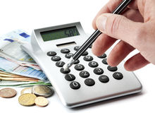 Counting money with calculator Royalty Free Stock Image