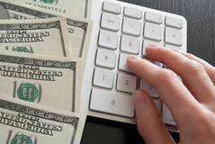 Counting money on computer calculator Royalty Free Stock Photos