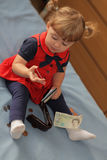 Counting money. Little baby girl counting money taken out of her mom wallet Stock Image