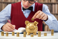 Counting money. Young accountant male counting money and putting in piggy bank royalty free stock images