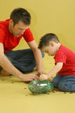 Counting Pennies. Man and child putting pennies in piggy bank Stock Images