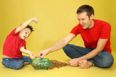 Counting Pennies. Man and child putting pennies in piggy bank Royalty Free Stock Photos