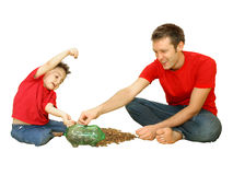 Counting Pennies. Man and child putting pennies in piggy bank Stock Image