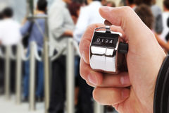 Counting people. Hand held tally counter counting headcount of people in a queue stock photo