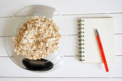 Counting and recording the amount of calories, proteins, carbohydrates and fats in food. Flakes from four cereals on kitchen. Scales. Oatmeal, wheat, barley and stock image