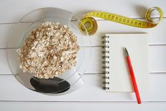 Counting and recording the amount of carbohydrates, calories, proteins and fats in food. Flakes from four cereals on kitchen stock photo