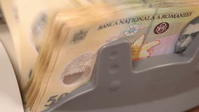 Counting romanian fifty lei bills - front view of counter machine stock video footage