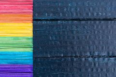 Counting sticks of the rainbow color on a dark blue. Counting sticks of the rainbow color on a dark blue wooden background on the left Stock Images