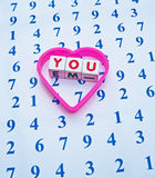 Counting on you. Text '  you ' in red uppercase letters on small white cubes surrounded by a heart shape  and placed upon a sheet with an array of blue numbers Royalty Free Stock Photo