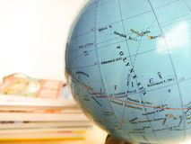 Countries and continents close up with the color map on a globe with books in the background. Education and travel concept stock photos