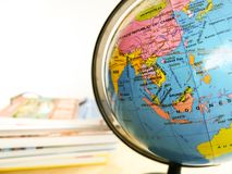 Countries and continents close up with the color map on a globe with books in the background. Education and travel concept royalty free stock images