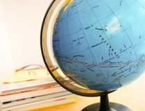 Countries and continents close up with the color map on a globe with books in the background. Education and travel concept stock photo