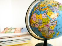 Countries and continents close up with the color map on a globe with books in the background. Education and travel concept royalty free stock photography