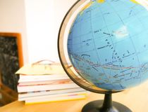 Countries and continents close up with the color map on a globe with books in the background. Education and travel concept royalty free stock photos