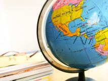Countries and continents close up with the color map on a globe with books in the background. Education and travel concept stock images