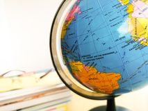 Countries and continents close up with the color map on a globe with books in the background. Education and travel concept royalty free stock image