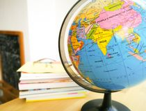Countries and continents close up with the color map on a globe with books in the background. Education and travel concept royalty free stock photo