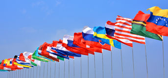 Countries flag in line. Different countries national flags getting together under blue sky, shown as worldwide, country, and international communication or stock photography
