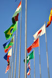 Countries flags flying. Different countries national flags on pole together, shown as worldwide, country, and international communication or activities royalty free stock photo