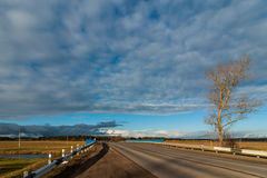 country asphalt automobile road under the original cloudy sky Stock Image