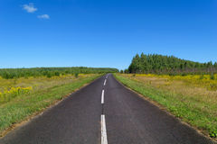 Country asphalt highway with one line of dashed white road markings Royalty Free Stock Images