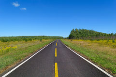 Country asphalt highway with one line of dashed yellow and two line of solid white road markings Royalty Free Stock Photography