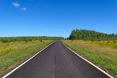 Country asphalt highway with two line of solid white road markings Stock Photos