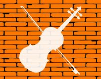 Country Background With Red Brick Wall. A well worn wall painted with a country fiddle in white Royalty Free Stock Image