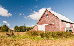 Country barn in autumn field. An old, weather beaten, farm barn in an open country field on a bright, sunny autumn day Stock Image