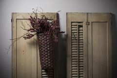 Country Basket Hanging on Old Shutters Stock Photos