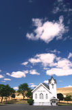 Country Bible Church. Old white country church with wheat fields and blue sky with puffy clouds Royalty Free Stock Photo