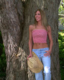 Country blonde Gal. Enjoying the outdoors in  a pink tube top and jeans Royalty Free Stock Photos
