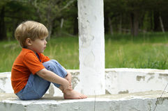 Country Boy. A child sits on the edge of a fountain stock images