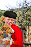 Country Boy abd His Collie. A boy holding his dog in the farm yard stock photo