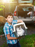 Country boy with cat in carrier going to travel car. Country preteen boy with cat in carrier going to travel by car Royalty Free Stock Images