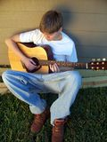 Country Boy Playing Guitar. Daniel likes to play his guitar to relax Stock Images