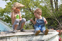 Country boys laughing and playing in the summer. Two small town boys are blowing bubbles on an old car. The older boy is wearing a straw hat and no shirt. The royalty free stock photo