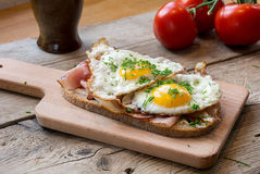 Country bread with ham and fried egg on a rustic table Royalty Free Stock Photos