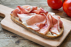 Country bread with smoked ham bacon on a wooden board Royalty Free Stock Image