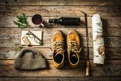 Country cabin - boots, warm hat, tea, book and firewood. Winter or christmas weekend in country cottage cabin concept. Boots, warm hat, hot drink and firewood royalty free stock photography