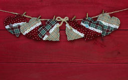 Country Christmas hearts hanging on clothesline against antique red wooden background Royalty Free Stock Images