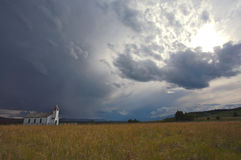 Country Church. Small country church standing alone in the field with stormy sky Stock Photography